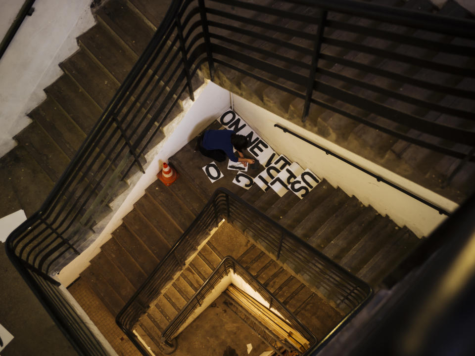 In this Oct. 23 2019 photo, a woman paints some slogans against domestic violence in the stairwell of a building in Paris. Domestic violence rates in France are higher than those in many other European countries, and activists say authorities often fail to protect women. (AP Photo/Kamil Zihnioglu)