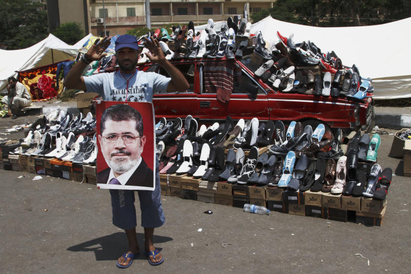 A supporter of Egypt's ousted President Mohammed Morsi waves in front of a car turned into a stand selling shoes in Nasser City, suburb of Cairo, Egypt, Sunday, July 7, 2013. Egypt's new president moved to assert his authority and regain control of the streets Saturday even as his Islamist opponents declared his powers illegitimate and issued blood oaths to reinstate Mohammed Morsi, whose ouster by the military has led to dueling protests and deadly street battles between rival sides. (AP Photo/Paul Schemm)