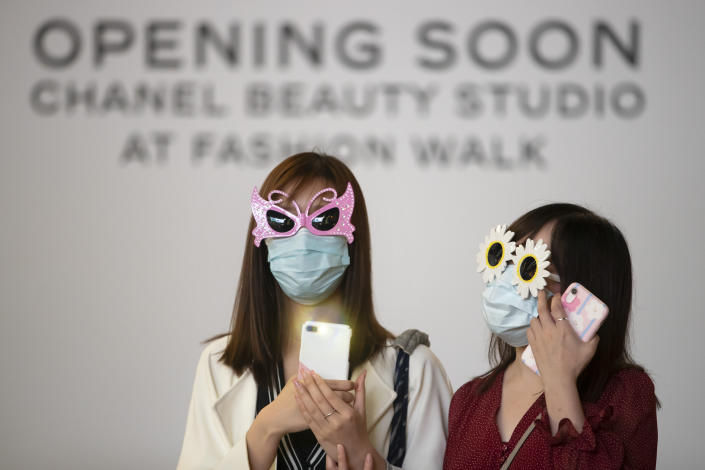 Women wearing masks and sunglasses attend a protest in Hong Kong, Friday, Oct. 18, 2019. Hong Kong pro-democracy protesters are donning cartoon and superhero masks as they formed a human chain across the semiautonomous Chinese city, in defiance of a government ban on face coverings. (AP Photo/Mark Schiefelbein)