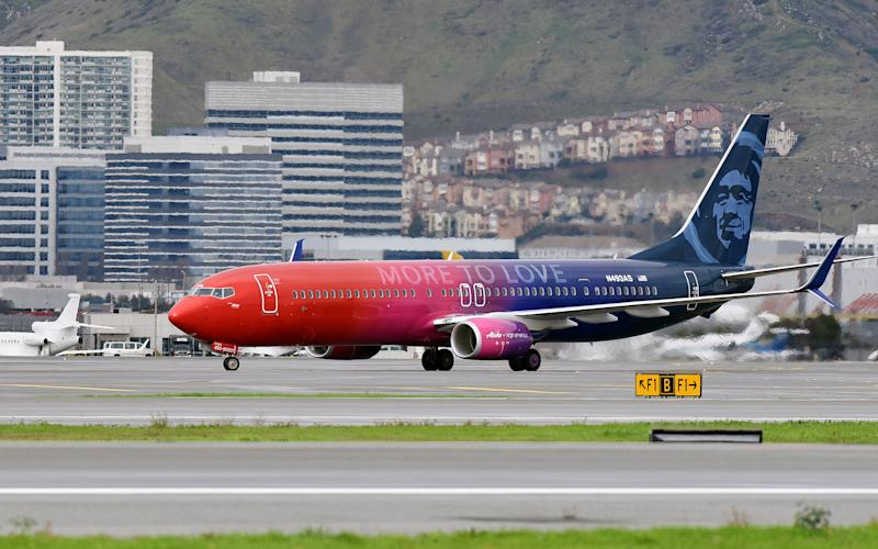 "A specially painted, co-branded Alaska Airlines and Virgin America 737-900ER aircraft, painted in shimmering red, purple and blue and featuring the slogan ""More to love,"" lands at San Francisco International Airport"