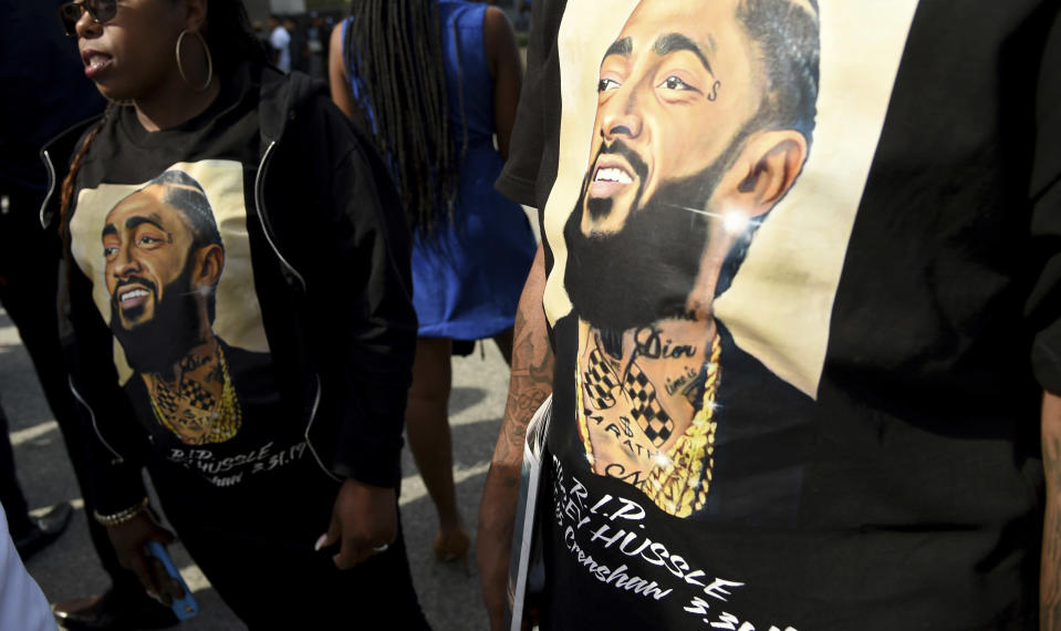 FILE - In this April 11, 2019 file photo, mourners wear T-shirts in tribute to Nipsey Hussle at a memorial service for the rapper at the Staples Center in Los Angeles. Hussle, 33, was shot and killed outside his Los Angeles clothing store on March 31, 2019. A year after Hussle's death, his popularity and influence are as strong as ever. He won two posthumous Grammys in January, he remains a favorite of his hip-hop peers and his death has reshaped his hometown of Los Angeles in some unexpected ways. (Photo by Chris Pizzello/Invision/AP, File)