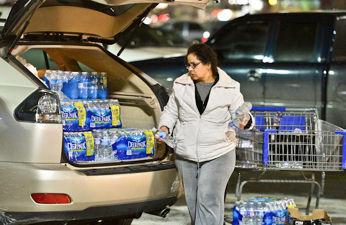 Charleston resident Niru Parikshak loads up the back of her car with bottled water Thursday Jan. 9, 2014 in Charleston, W.Va. . Sam's Club and every retailer for a twenty mile radius sold out of bottled water after a chemical leak Thursday morning up river from the WV American Plant on the Elk River forced the water plant to shut down. (AP Photo/Charleston Daily Mail, Bob Wojcieszak)