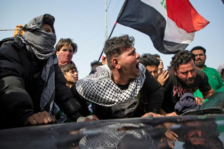 Angry Iraqi demonstrators mourn the killing of female activist and paramedic Janat Madhi, in Basra on Tuesday night, part of an upsurge of violence against the three-month-old protest movement