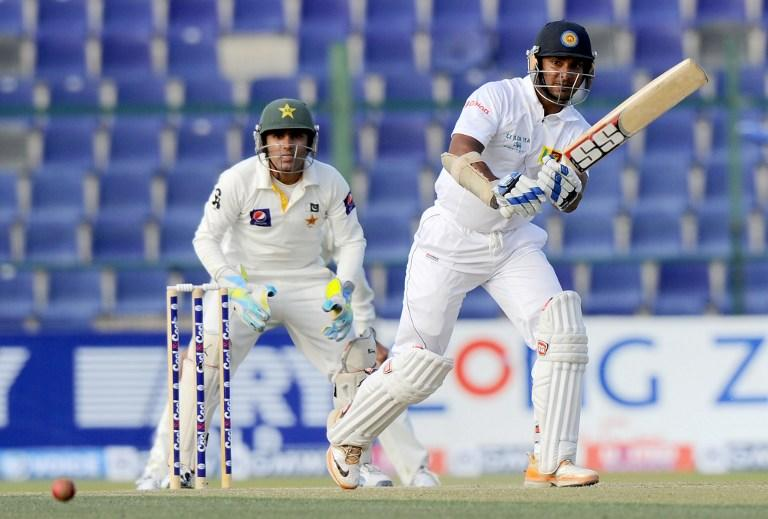Sri Lankan batsman Kumar Sangakkara plays a shot as Pakistan wicketkeeper Adnan Akmal (L) looks on during the third day of the first cricket Test match between Pakistan and Sri Lanka at the Sheikh Zayed Stadium in Abu Dhabi on January 2, 2014. Pakistan's last six wickets fell cheaply on the third morning of the first Test and restrict them to 383. Sri Lanka's first-innings 204 but had to settle for a still-useful 179-run advantage. AFP PHOTO/Ishara S. KODIKARA