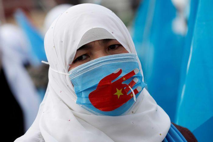 A woman wearing a headscarf and a face mask at a protest