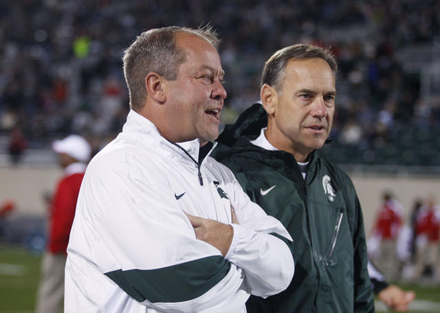 FILE - In this Oct. 22, 2011, photo, Michigan State athletic director Mark Hollis, left, talks with football coach Mark Dantonio before an NCAA college football game against Wisconsin in East Lansing, Mich. In a memo proposing updates to the Uniform Athlete Agents Act, athletics officials suggest increased penalties and broadening the law's reach to include financial advisers and others who might not classify themselves as an agent. Hollis, who supports the memo's proposals, is in one of the few states that doesn't have the agent law. The proposed changes come as authorities in North Carolina pursue criminal cases against an agent and a former UNC tutor for violating state sports agent laws by providing benefits to former Tar Heels football players in 2010. (AP Photo/Al Goldis, File)