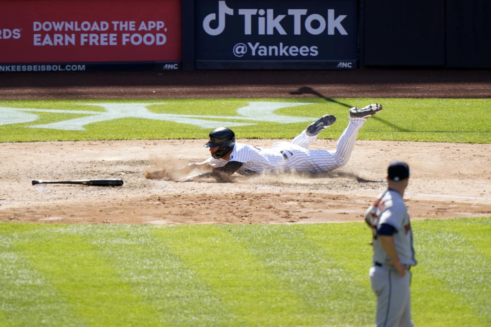 Houston Astros relief pitcher Ryan Pressly, foreground, watches as New York Yankees' Gleyber Torres scores on Aaron Hick's infield single during the eighth inning of a baseball game, Thursday, May 6, 2021, at Yankee Stadium in New York. (AP Photo/Kathy Willens)