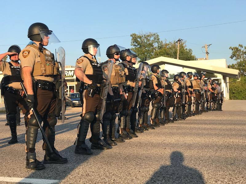 Riot police stand in a line near protesters in St. Louis County.