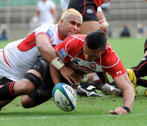 Tonga's scrum-half Taniela Moa (L) tackles Japan's centre Ryan Nicholas