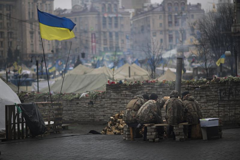 """Anti-Yanukovych protesters warm themselves next to a fire in Kiev's Independence Square, Ukraine, Wednesday, March 5, 2014. Stepping back from the brink of war, Vladimir Putin talked tough but cooled tensions in the Ukraine crisis Tuesday, saying Russia has no intention """"to fight the Ukrainian people"""" but reserves the right to use force. As the Russian president held court in his personal residence, U.S. Secretary of State John Kerry met with Kiev's fledgling government and urged Putin to stand down. (AP Photo/Emilio Morenatti)"""