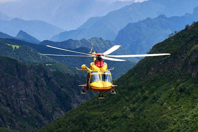 Italian rescueing helicopter reaching accident location in the alps