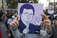 Pro-democracy protesters hold a sketch of activist Arnon Nampha and shouting release our friends during a protest in Bangkok, Thailand, Saturday, Feb. 20, 2021. The protesters are calling for Prime Minister Prayuth Chan-ocha to step down hours after he survived a no-confidence vote in parliament amid allegations that his government mismanaged the economy, bungled the provision of COVID-19 vaccines, abused human rights and fostered corruption.(AP Photo/Sakchai Lalit)
