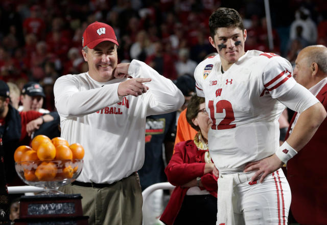 FILE - In this Dec. 30, 2017, file photo, Wisconsin head coach Paul Chryst and quarterback Alex Hornibrook (12) stand next to the MVP trophy at the end of the Orange Bowl NCAA college football game against Miami, in Miami Gardens, Fla. Hornibrook won the MVP trophy. Spring is in the air for the Wisconsin's usually run-first offense. Coach Paul Chryst is letting loose a little bit more in spring practice, which makes sense given quarterback Hornibrook's bowl performance and a stocked receiving corps. (AP Photo/Lynne Sladky, File)