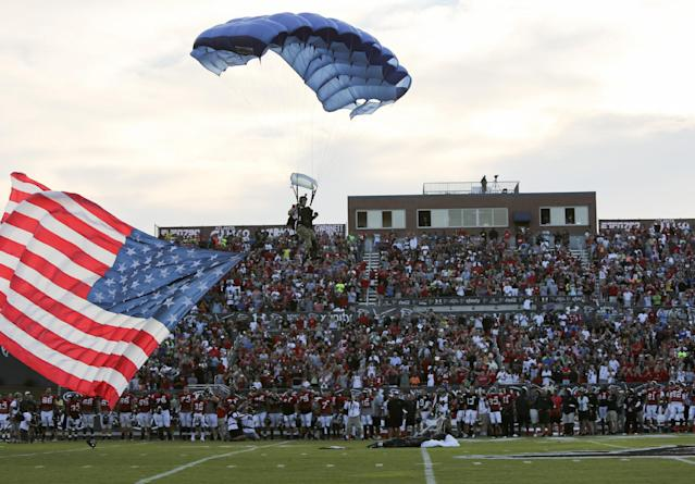A skydiver lands on the football field with a U.S. flag before the Atlanta Falcons' Friday Night Lights, at Archer High School on Friday, Aug. 1, 2014, in Lawrenceville, Ga. The Falcons continued their tradition of staging NFL football practice at an area high school each year. (AP Photo/Jason Getz)