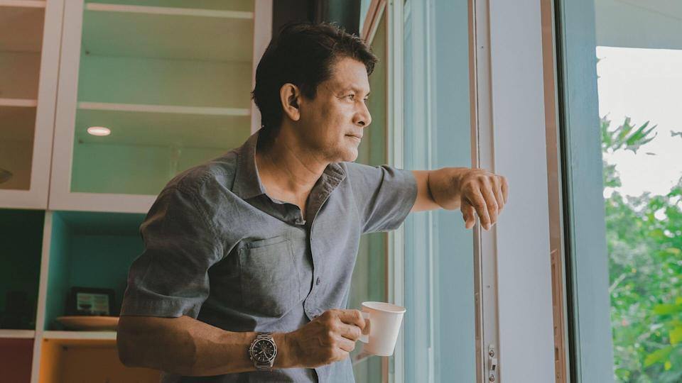 Middle aged Asian man looking out a window, sipping coffee and using ideas.