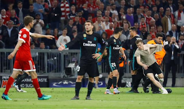 Soccer Football - Champions League Semi Final First Leg - Bayern Munich vs Real Madrid - Allianz Arena, Munich, Germany - April 25, 2018 Stewards tackle a pitch invader after the match as Real Madrid's Cristiano Ronaldo looks on REUTERS/Kai Pfaffenbach