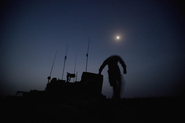 <p>PVT Jay Mora, of Quebec, Canada, with the Canadian Army's 1st Battalion 22nd Royal Regiment, dismounts from a light armored vehicle under the moonlight in preparation for an operation, June 26, 2011 at Forward Operating Base Kyhber in the Panjwaii district of Kandahar province, Afghanistan. (AP Photo/David Goldman) </p>