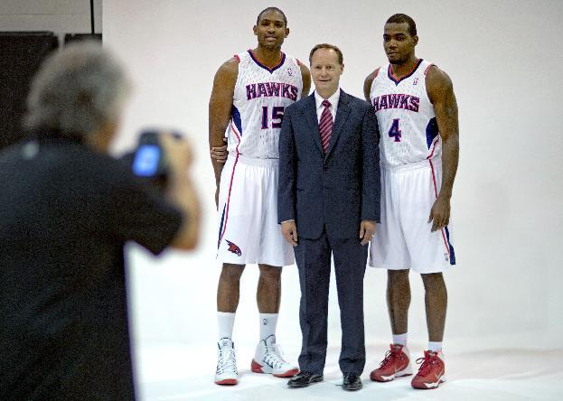 Atlanta Hawks head coach Mike Budenholzer, center, poses for a photographer with Al Horford, left, and Paul Millsap, during the team's NBA basketball media day, Monday, Sept. 30, 2013, in Atlanta. (AP Photo/David Goldman)