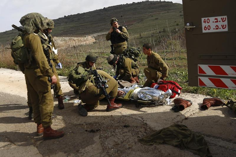 A wounded Israeli soldier is treated in the Golan Heights, Tuesday, March 18, 2014. A roadside bomb hit an Israeli patrol near the frontier with the Golan Heights on Tuesday, the army said, wounding four soldiers in the most serious violence to strike the area since the Syrian conflict began three years ago. Israel said it responded with artillery strikes on Syrian army targets. Israel captured the Golan Heights from Syria in the 1967 Middle East war and later annexed the strategic area in a move that was not internationally recognized. (AP Photo/Jinipix) ****ISRAEL OUT***
