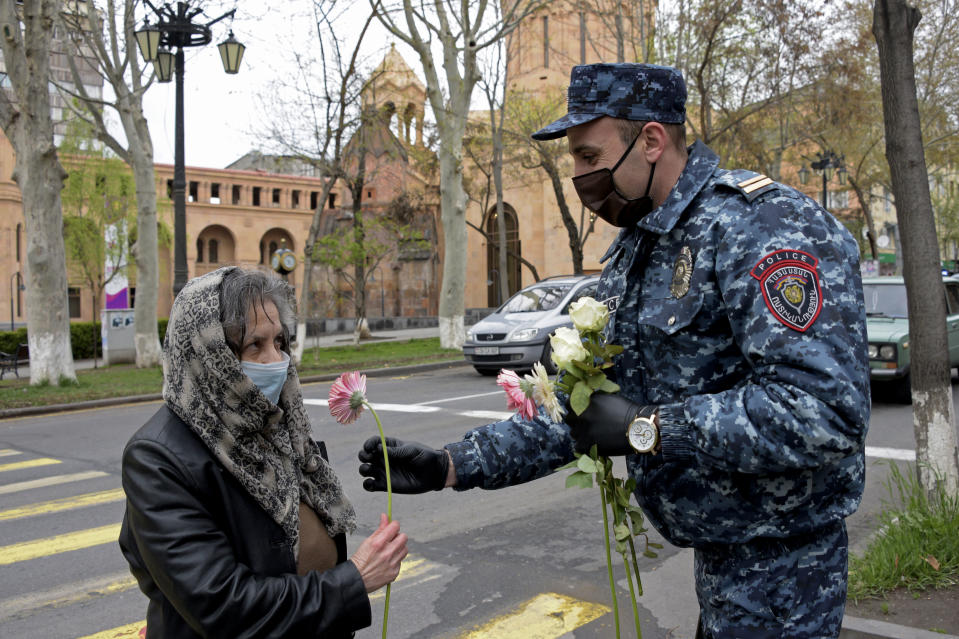 TOPSHOT - A police officer wearing a face mask and gloves presents a flower to a woman on the Motherhood and Beauty Day in downtown Yerevan on April 7, 2020, amid the spread of the COVID-19 coronavirus. (Photo by KAREN MINASYAN / AFP) (Photo by KAREN MINASYAN/AFP via Getty Images)