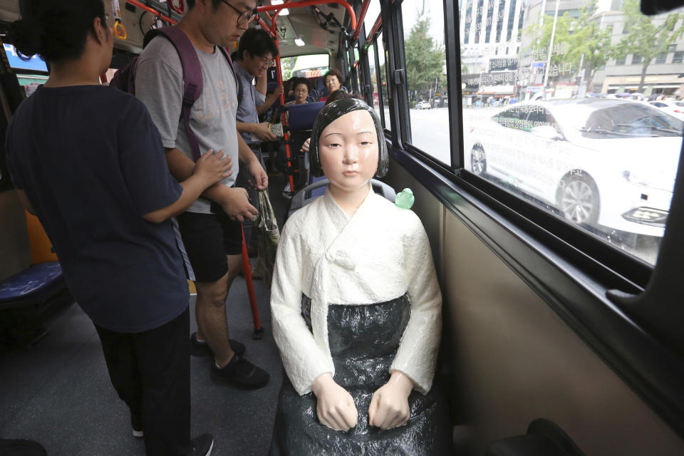 "FILE - In this Aug. 14, 2017, file photo, a comfort woman statue is placed on a chair of a bus to mark the 5th International Memorial Day for Comfort Women, in Seoul, South Korea. Japanese Foreign Minister Toshimitsu Motegi, in his diplomatic speech on Monday, Jan. 18, 2021 said a recent South Korean court ruling ordering Japan's government to pay compensation to 12 South Korean former ""comfort women"" over World War II-era sexual abuses by Japanese troops was ""an abnormal development absolutely unthinkable under international law and bilateral relations."" (AP Photo/Ahn Young-Joon, File)"