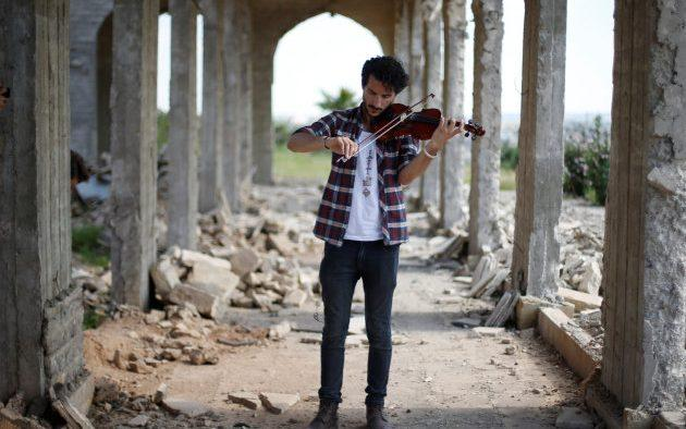 Ameen Mukdad, a violinist from Mosul who lived under Isil's rule for two and a half years where they destroyed his musical instruments, performs at Nabi Yunus shrine in eastern Mosul, Iraq - Credit: Reuters