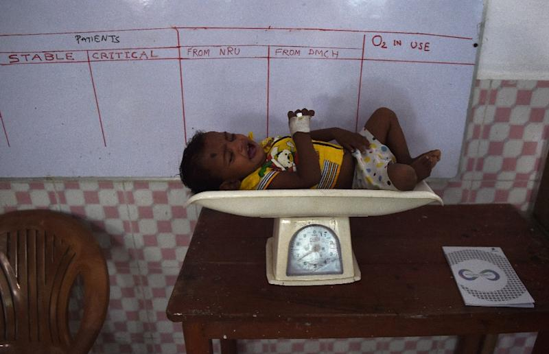 A malnourished child lies on a weighing scale at the Nutritional Rehabilitation Centre at Darbhanga Medical College and Hospital in the eastern Indian state of Bihar