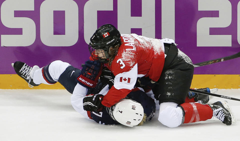 Jocelyne Larocque of Canada (3) gets tangled up with Monique Lamoureux of the United States (7) during the first period of the women's gold medal ice hockey game at the 2014 Winter Olympics, Thursday, Feb. 20, 2014, in Sochi, Russia. (AP Photo/Julio Cortez)