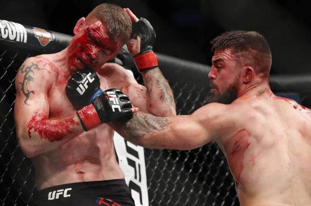 Mike Perry, right, hits Paul Felder during a welterweight mixed martial arts bout at UFC 226, Saturday, July 7, 2018, in Las Vegas. (AP Photo/John Locher)