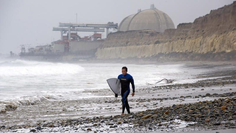With the San Onofre Nuclear Generating Station as a backdrop, Huy Pham of San Juan Capistrano walks south along the beach at San Onofre State Beach early Friday morning, June 7, 2013, after it was announced that the nuclear plant will be closing permanently. (AP Photo/The Orange County Register, Mark Rightmire) MAGS OUT; LOS ANGELES TIMES OUT