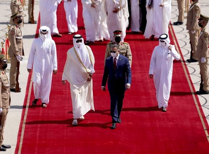 A photo released by the Iraqi Prime Minister Media Office shows Iraqi Prime Minister Mustafa al-Kadhimi, center, welcomes Qatar's Emir Sheikh Tamim bin Hamad Al Thani, center left, before the Baghdad Conference for Cooperation and Partnership in Baghdad, Saturday, Aug. 28, 2021. (Iraqi Prime Minister Media Office, via AP)