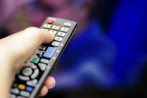 Closeup of a hand holding a remote control for the television.