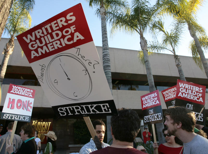 FILE - In this Feb. 8, 2008 file photo, members of the Writers Guild of America talk about the possibility of a new contract, as they walk on the picket line at NBC Studios in Burbank, Calif. Hollywood is facing a cliffhanger after members of the Writers Guild of America voted overwhelmingly to authorize a strike that could begin as soon as May 2, the day after the current contract ends. The previous writers' strike lasted 100 days in 2007-08 and was costly to the businesses that serve Hollywood and to consumers expecting to be entertained. (AP Photo/Damian Dovarganes, File)