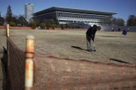 A man wearing a protective mask to help curb the spread of the coronavirus plays ground golf near the Tokyo Aquatics Center, one of the venues of Tokyo 2020 Olympic and Paralympic games, in Tokyo Wednesday, Jan. 20, 2021. The postponed Tokyo Olympics are to open in just six months. Local organizers and the International Olympic Committee say they will go ahead on July 23. But it's still unclear how this will happen with virus cases surging in Tokyo and elsewhere around the globe. (AP Photo/Eugene Hoshiko)