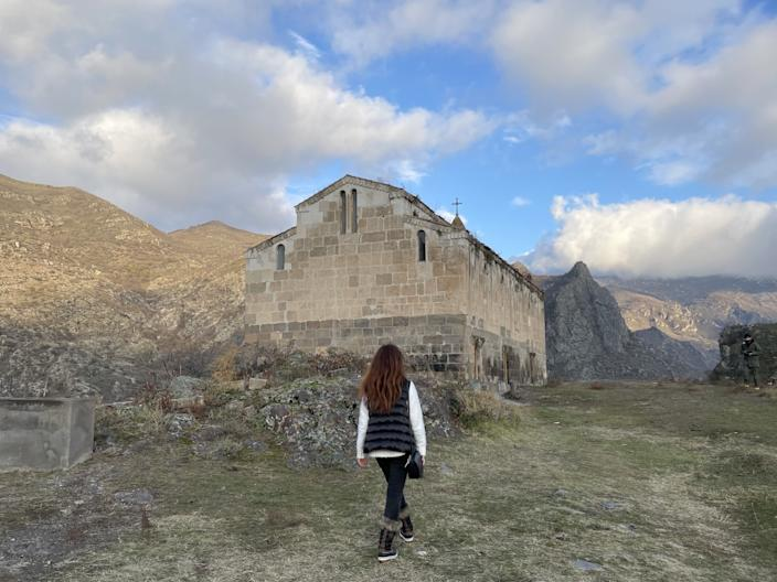A woman walks toward a stone monastery in Nagorno-Karabakh — known as Artsakh to Armenians.