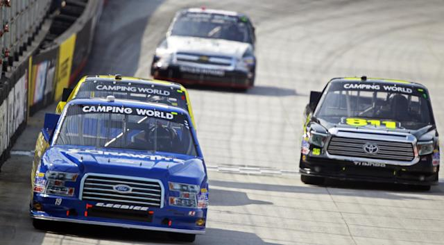 Driver Brad Keselowski (19) leads as he comes down the front straight during the NASCAR UNOH 200 Truck Series auto race on Thursday, Aug. 21, 2014, in Bristol, Tenn. (AP Photo/Wade Payne)