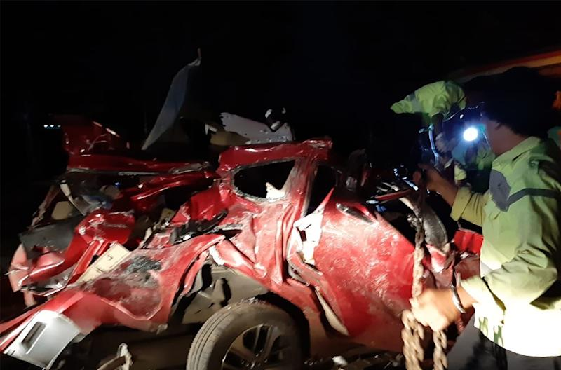 Police officers inspect the mangled wreck of one of the vehicles involved in a deadly Indonesian traffic accident