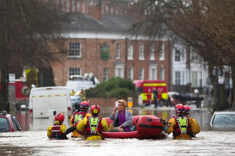A woman takes a photograph as she is transported to safety by members of the emergency services, after homes were affected by floodwaters in streets in York, northern England