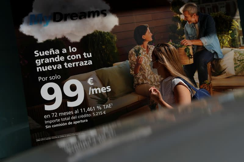 """A woman walks past a poster advertising Caixabank's consumer financing programme """"MyDreams"""" in Madrid"""