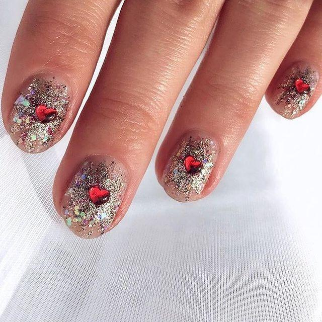 """<p>The best part about a glitter manicure is that it can be kind of haphazard and messy. But when you add a heart decal to the center of each nail, the look becomes edgy and cool.</p><p><a href=""""https://www.instagram.com/p/Bt30hv1hQNV/"""" rel=""""nofollow noopener"""" target=""""_blank"""" data-ylk=""""slk:See the original post on Instagram"""" class=""""link rapid-noclick-resp"""">See the original post on Instagram</a></p>"""