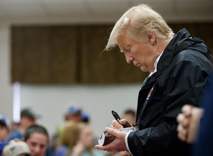 President Donald Trump signs a Bible as he greets people at Providence Baptist Church in Smiths Station, Ala., Friday, March 8, 2019, during a tour of areas where tornados killed 23 people in Lee County, Ala.