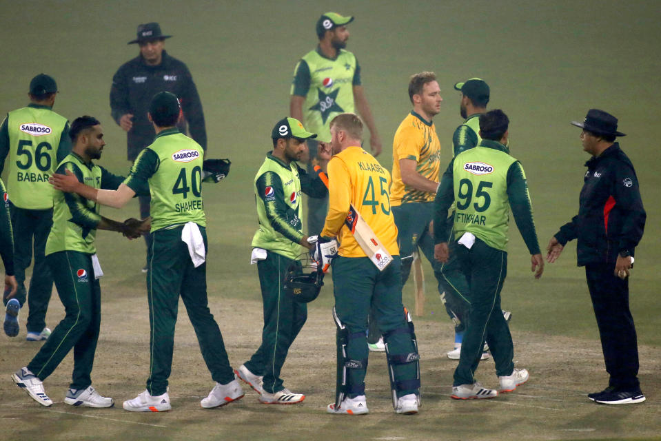 South Africa's Heinrich Klaasen, (45), and David Miller, fourth right, shake hand with Pakistani players on the end of their 2nd Twenty20 cricket match at the Gaddafi Stadium, in Lahore, Pakistan, Saturday, Feb. 13, 2021. (AP Photo/K.M. Chaudary)