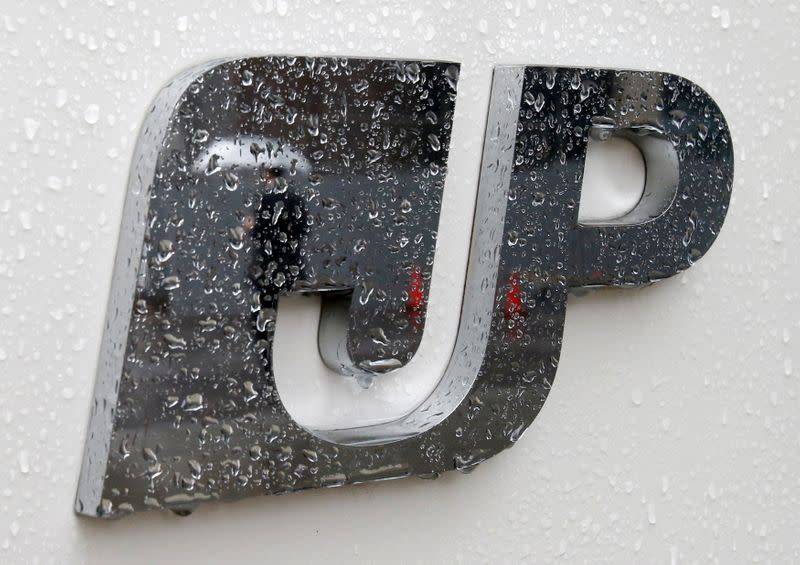 FILE PHOTO: FILE PHOTO:A man holding an umbrella is reflected in the logo of Japan Post Group at its headquarters in Tokyo