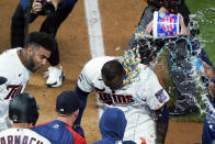 Minnesota Twins' Miguel Sano gets bubble gum poured on him following his walk-off, two-run home run against the Cincinnati Reds in the 12th inning of a baseball game, early Tuesday, June 22, 2021, in Minneapolis. The Twins won 7-5. (AP Photo/Jim Mone)