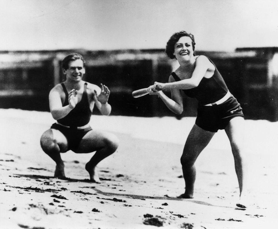 <p>Actors Joan Crawford and Douglas Fairbanks Jr. play baseball in their bathing suits on the beach, circa 1930. </p>