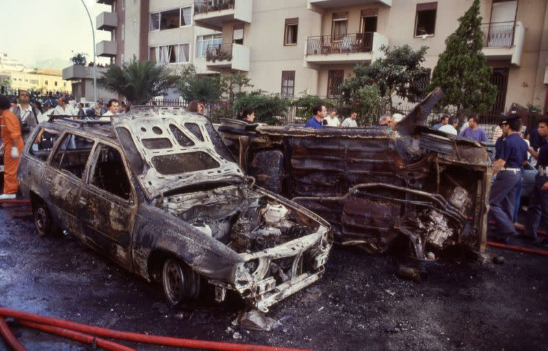 FILE PHOTO: Burned cars are seen after a bomb attack that killed judge Paolo Borsellino and his police guards in Palermo