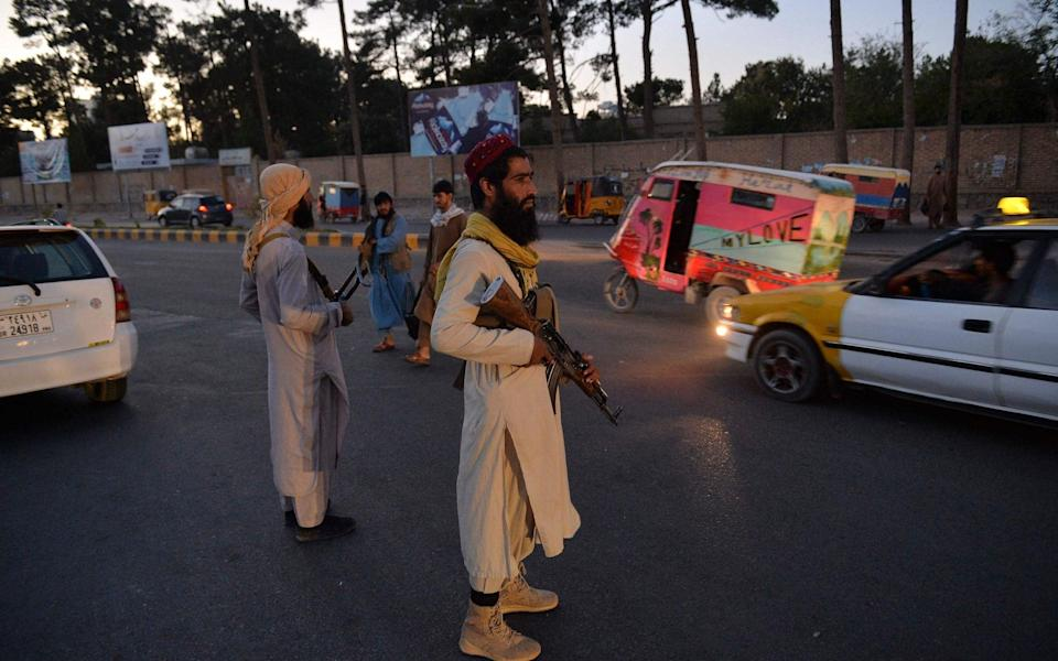 Taliban fighters stand guard along a road in Herat - HOSHANG HASHIMI /AFP