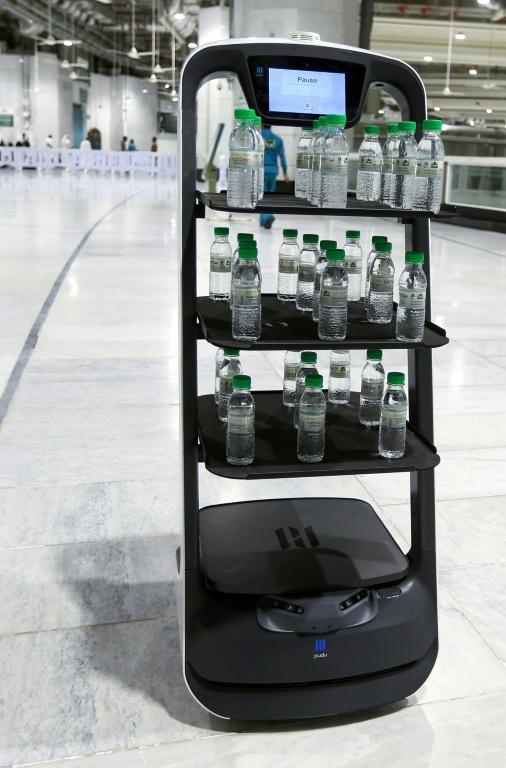 A smart robot supplies worshippers with bottles of Zamzam water to reduce direct contact with staff as a measure against Covid-19