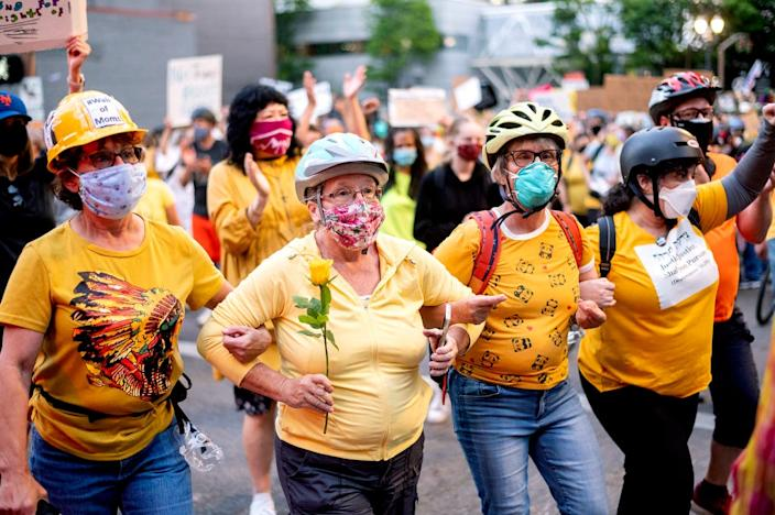 """Norma Lewis, holding flower, is a link in the """"wall of moms"""" during a Black Lives Matter protest on  July 20 in Portland, Ore."""