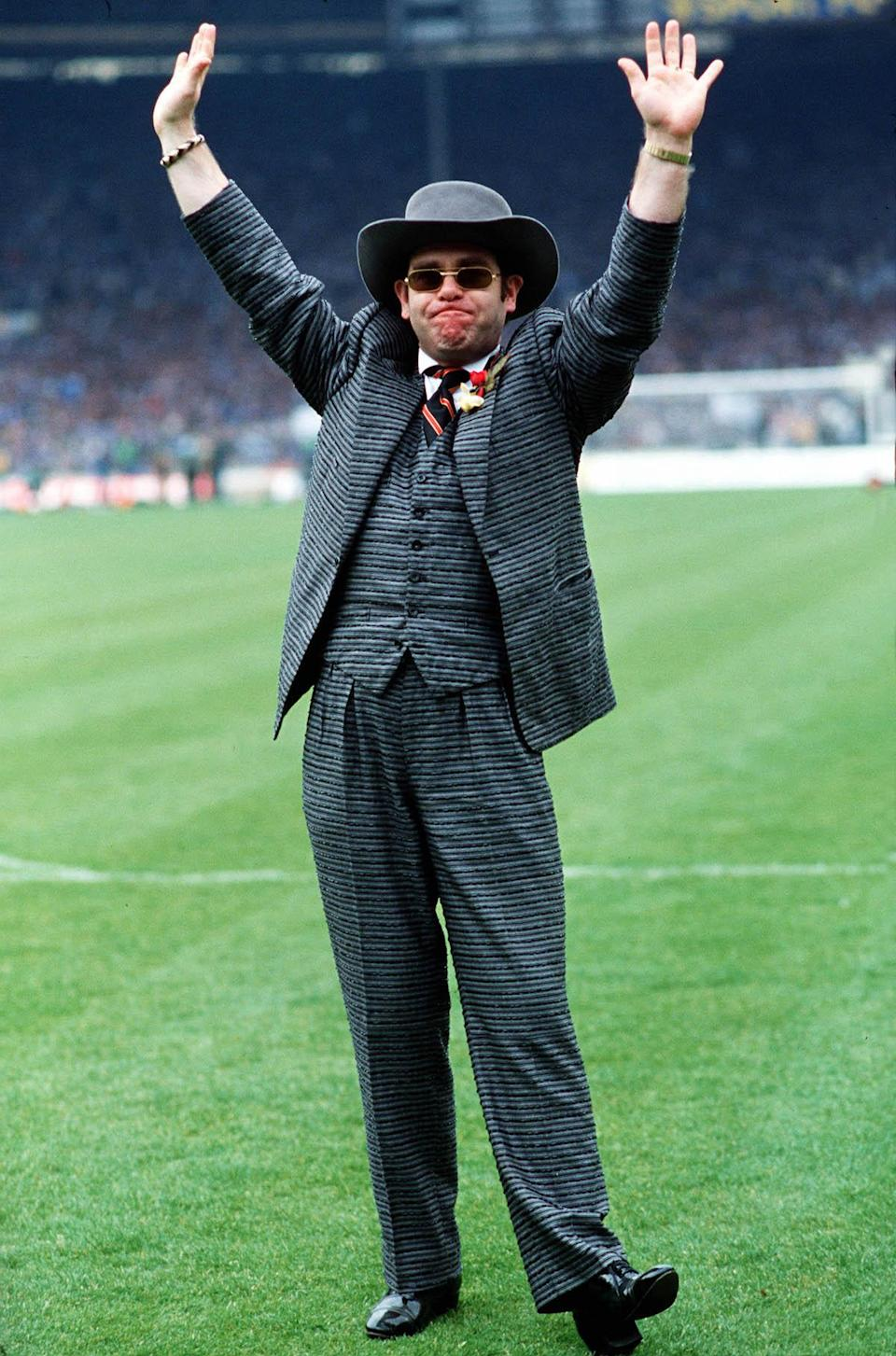 <p>Elton John in a fine English-style suit, waves to the fans at London's Wembley Stadium in 1984. (Photo: Getty Images) </p>